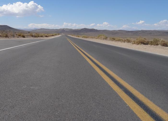 Een lange, uitzichtloze weg in Death Valley USA