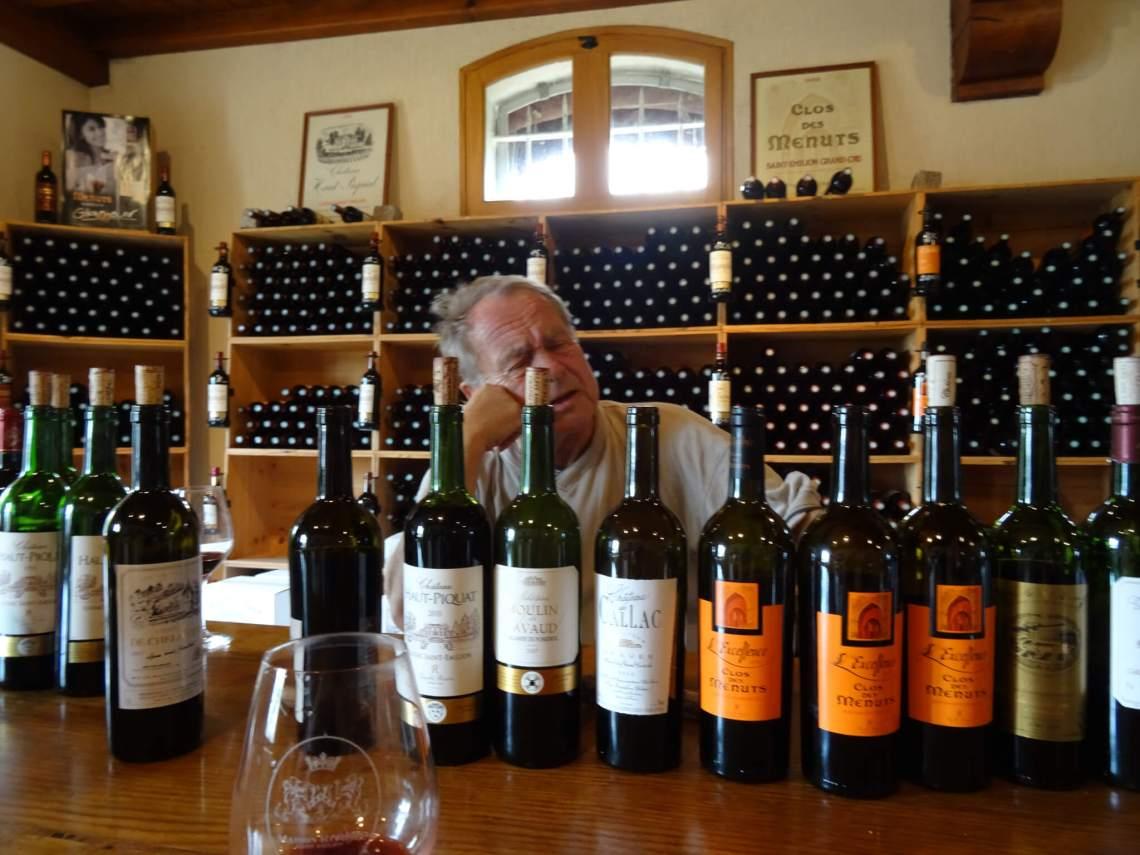 Verschillende soorten wijnen met daarachter chagrijnige wijnboer