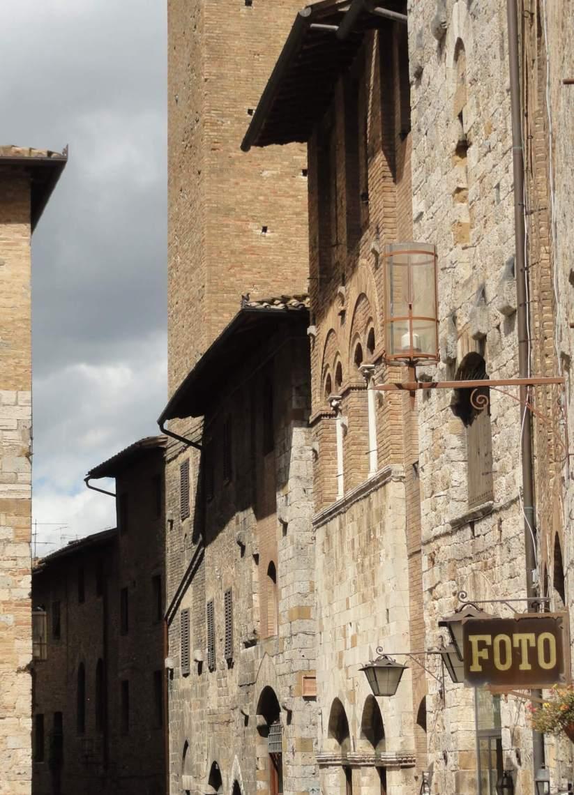 Gevels in San Gimignano met uithangbord waar foto op staat