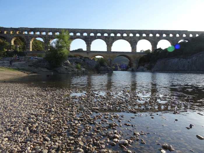 Rivierbedding met kiezels en Pont du Gard op de achtergrond