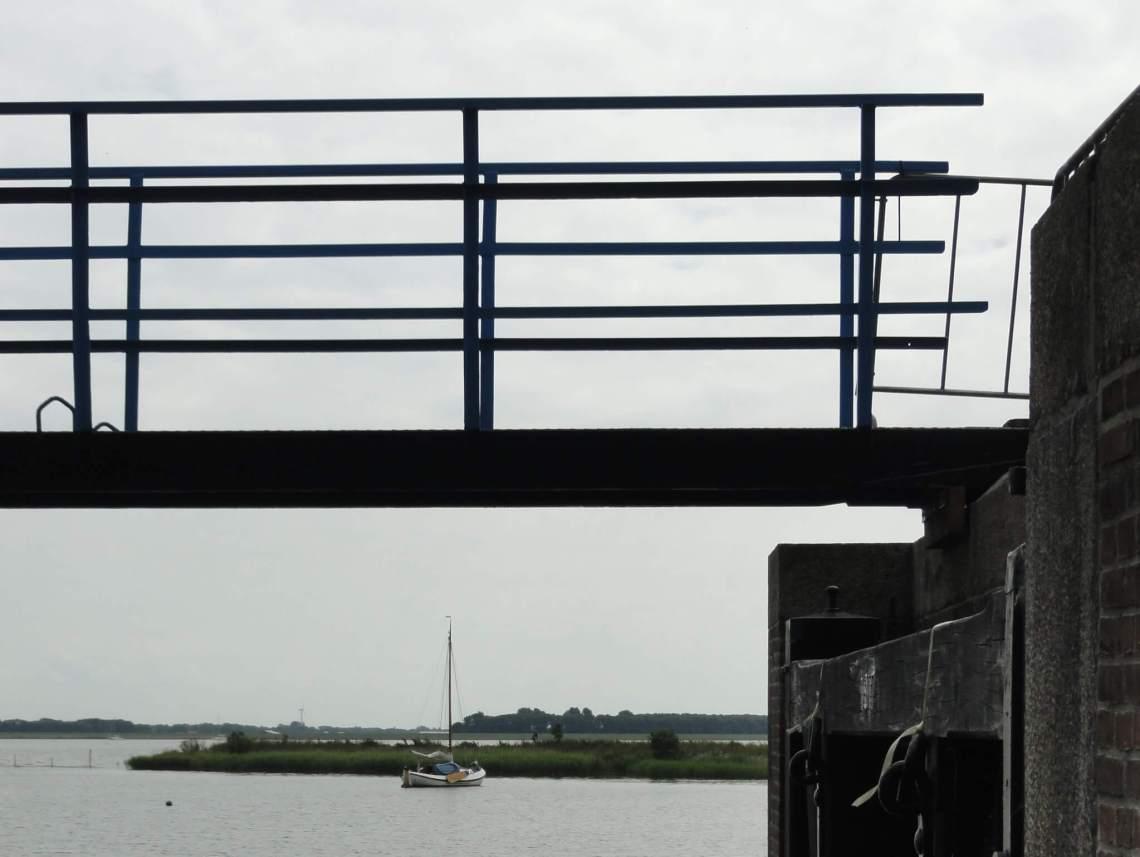 IJsselmeer met zeilboot gezien vanonder een brug tussen twee sluisdeuren