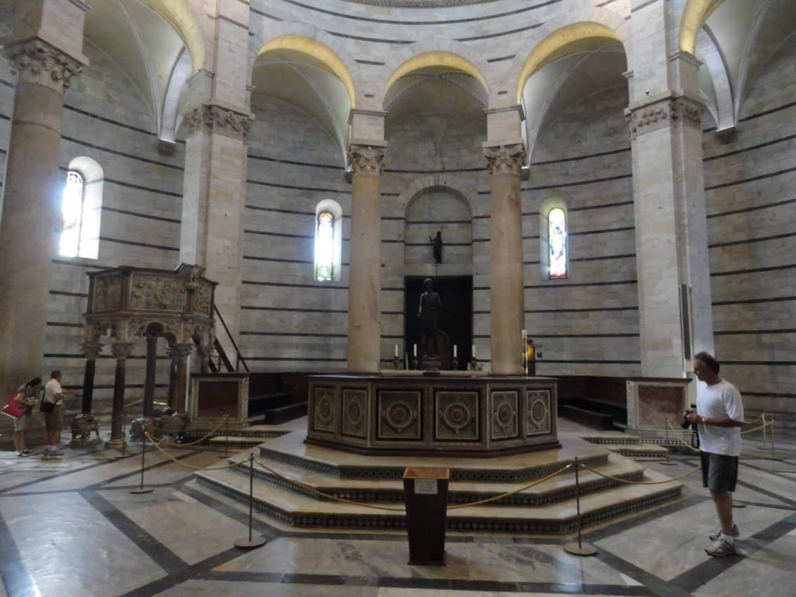 Achthoekig doopvont staande op een verhoging in Baptisterium Pisa