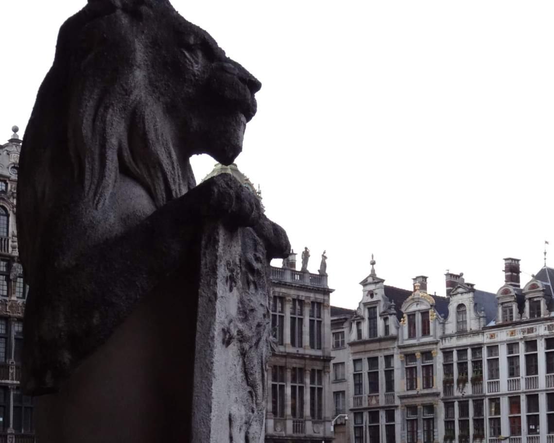 Stenen leeuw houdt een wapenschild vast  en kijkt uit over Grote Markt Brussel