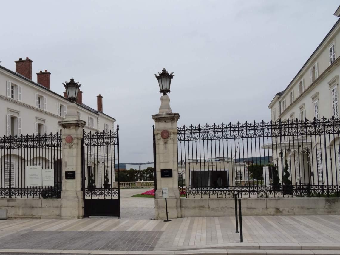 Luxe hekwerk met poort die leidt naar champagnehuis