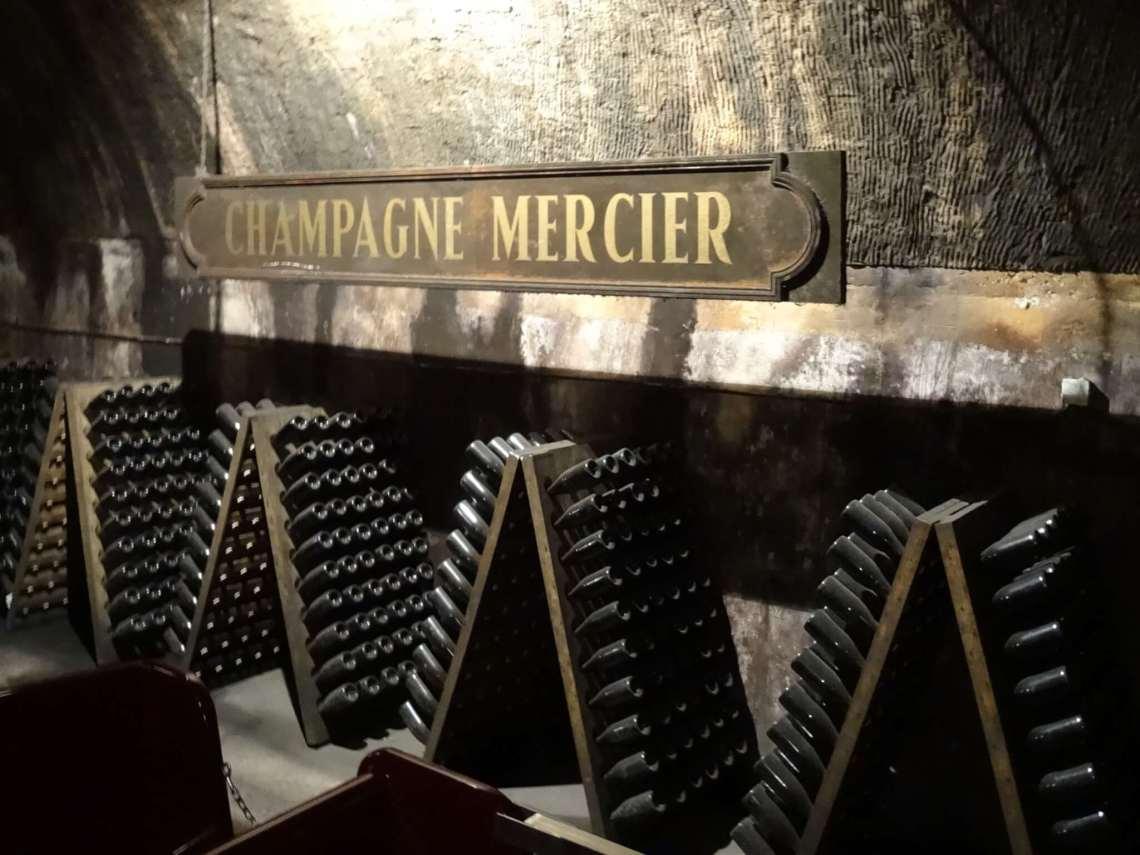 Flessen champagne in wijnrekken tegen elkaar aan