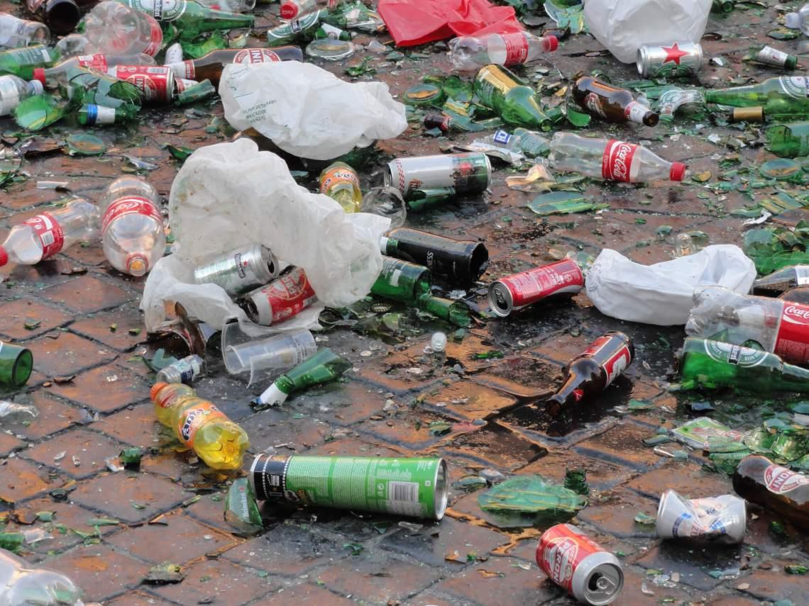 Straat vol met lege blikjes flesjes, scherven en plastic tasjes