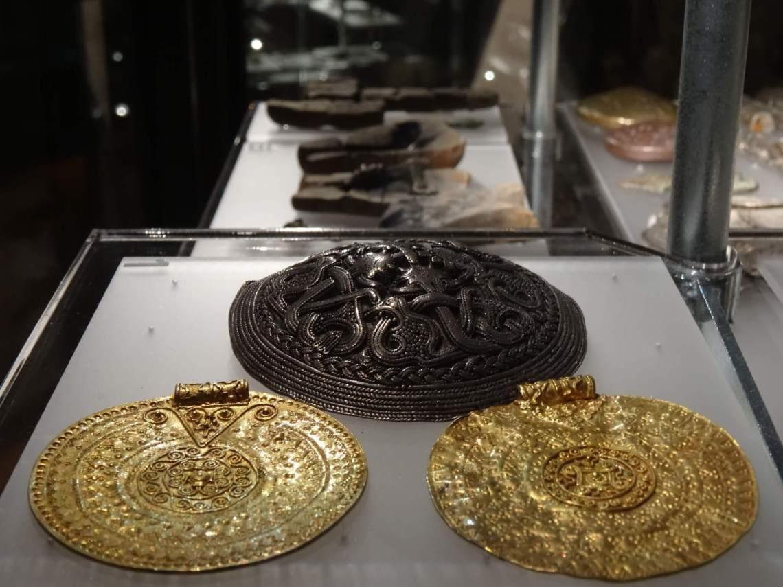 Twee gouden en een zilveren Vikingbroche in vitrinekastHovgården