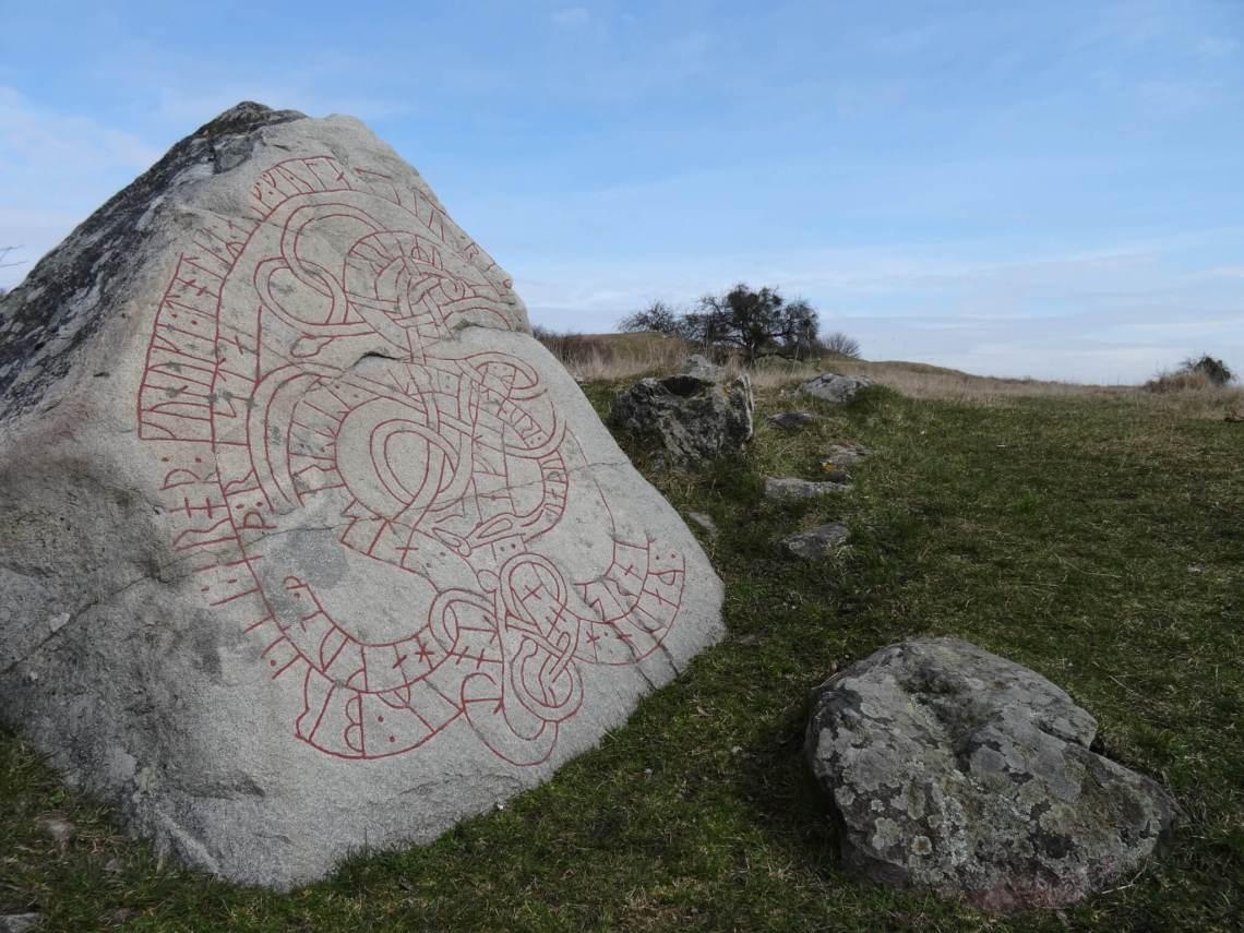 Runesteen waarop met rode verf in elkaar lopende slangen zijn getekend