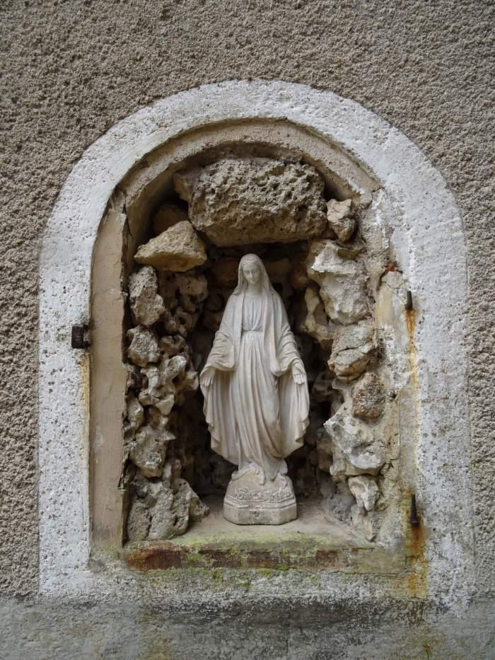 Beeldje van Maria Magdalena staande in een nis