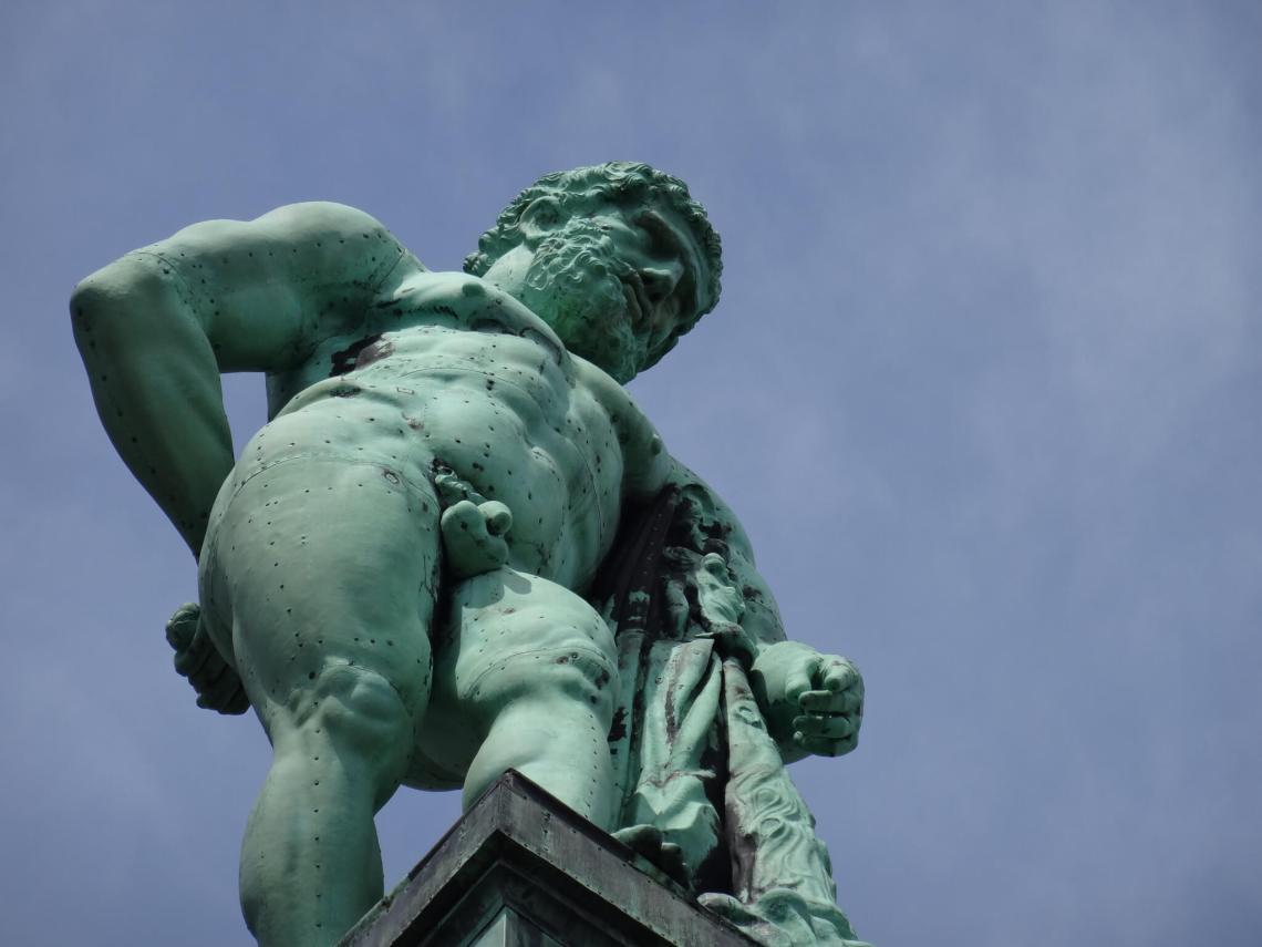 Naakte, groen uitgeslagen Hercules leunend op een knots