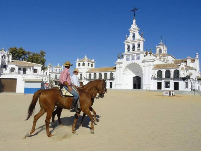 2 cowbous te paard passeren witte kerk in cowboydor El Rocio