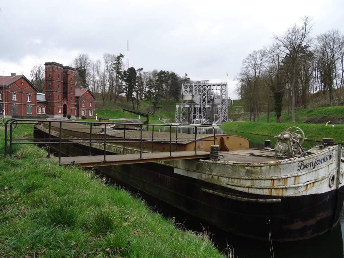 Oude schuit in Centrumkanaal met fabriek en een van de vier scheepsliften op de achtergrond