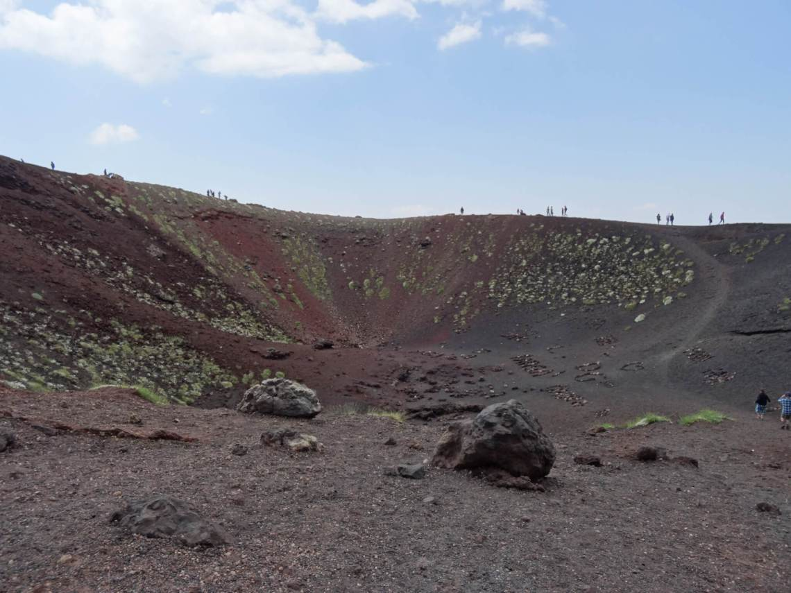 Kratermond met mensen zo groot als poppetjes die over de rand kijken