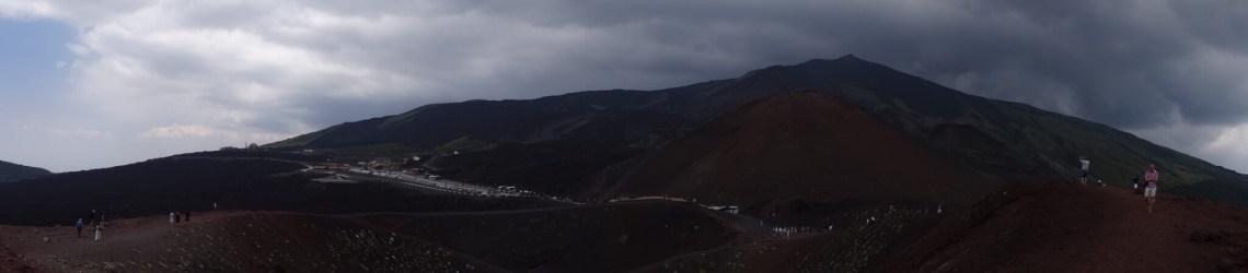 Dreigend zwarte wolken boven roodbruine Etna berg