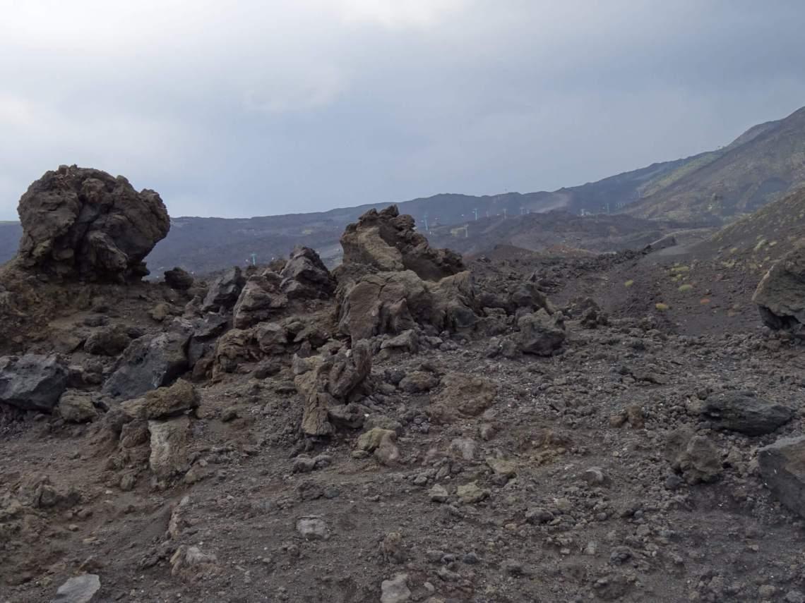 Bruin heuvellandschap met steenresten halverwege Etna vulkaan