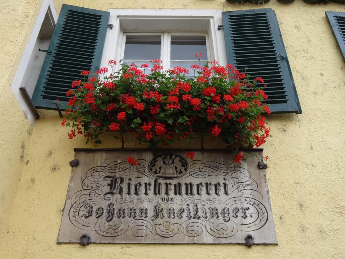 Raam met bloembak vol rode bloemen