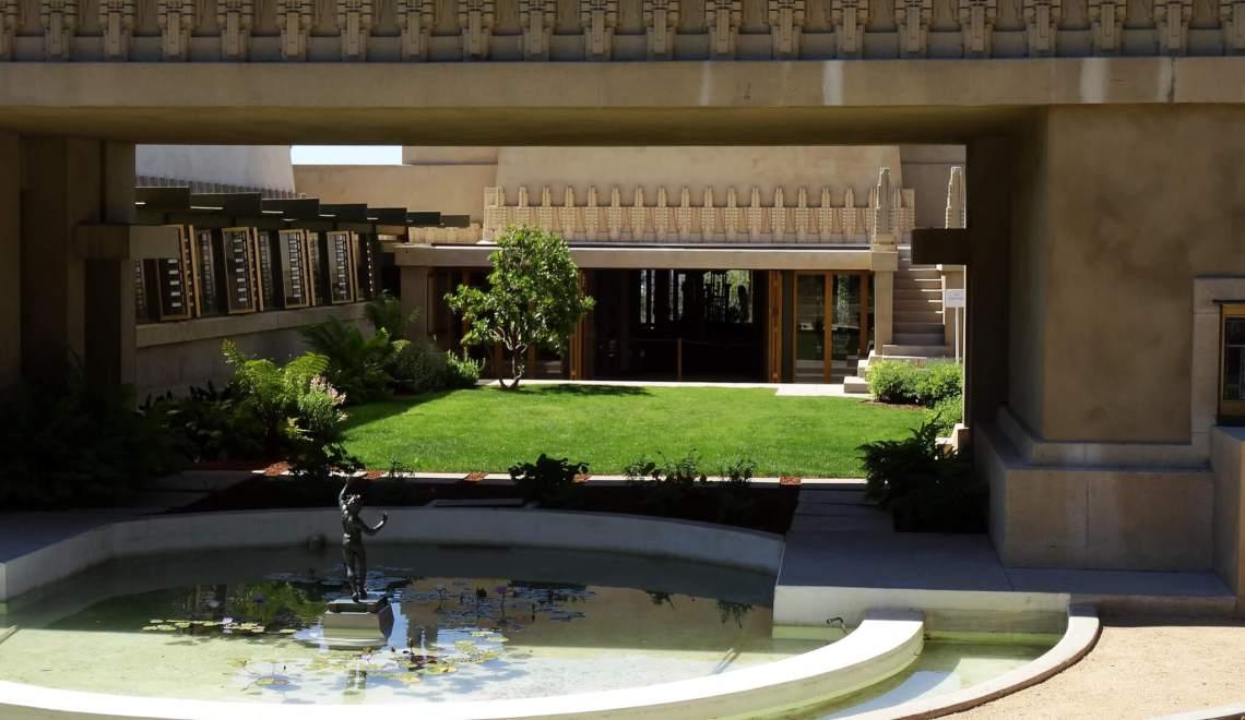 Vijver met beeld onder betonnen gevel van villa
