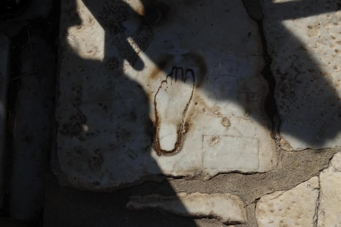 Voetafdruk in marmeren plaveisel