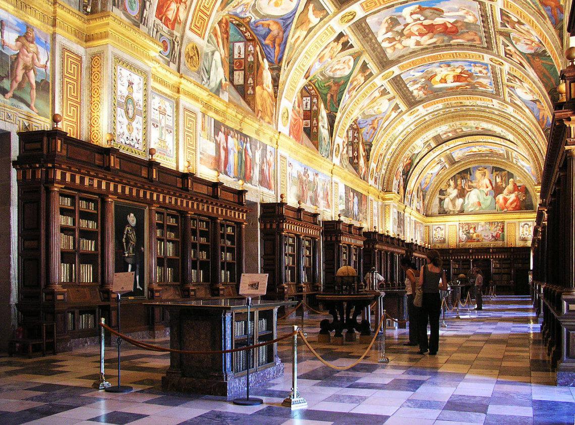 Kleurrijk beschilderd plafond boven boekenkasten en globe