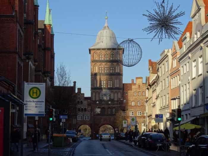 Straat met aan het einde bakstenen toren met ruiterdak