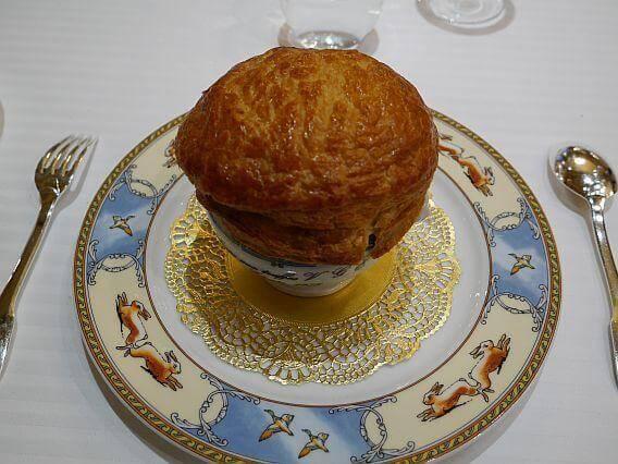 Truffelsoep op een bord met getekende konijnen, ganzen en gouden borduursel