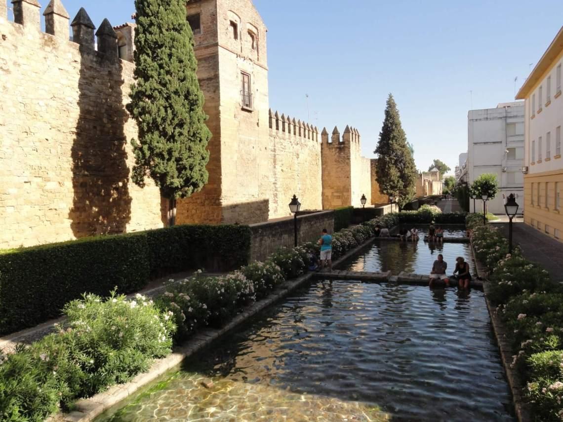 Pootje badende mensen naast de met kantelen bekroonde stadsmuur van Cordoba