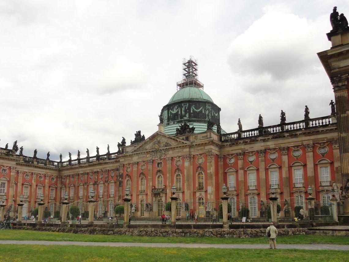 Roze achtergevel Neues Palais met hoge groenkoperen koepel en zwart beeldhouwwerk