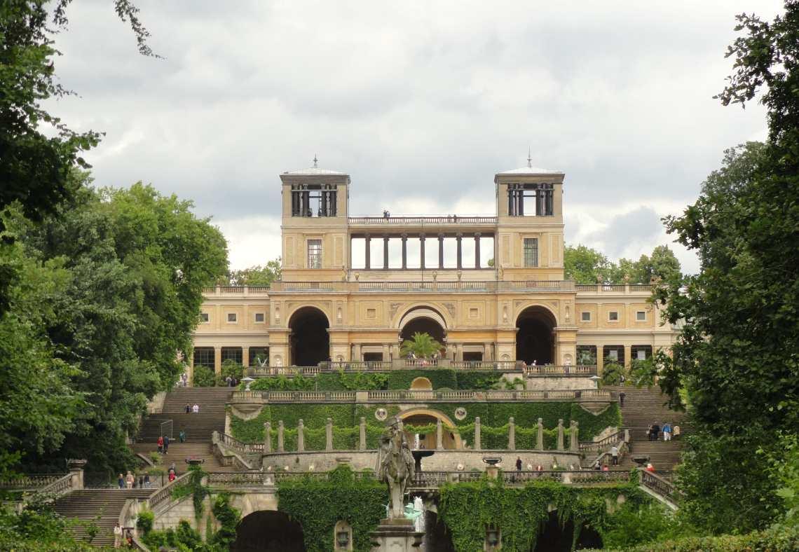 Met begroeiing omgeven trappen leiden naar paleis op de heuvel. Op de voorgrond een beeld van een ruiter