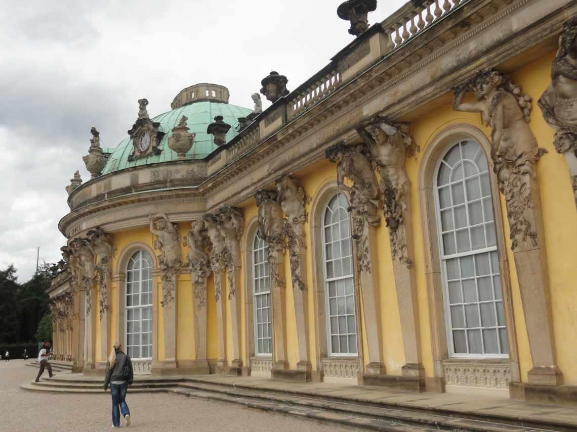 Gele achtergevel van Sansoucci paleis met koperen koepel, rijk beeldhouwwerk en halfronde vensters