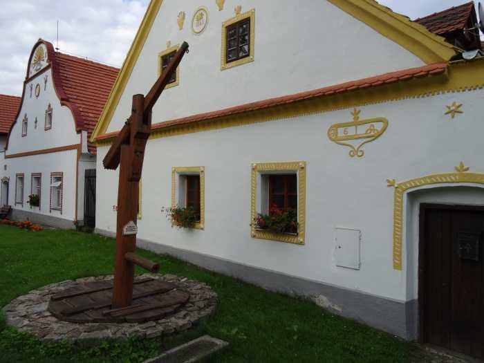 Houten waterpomp voor witte boerderij met gele omlijsting