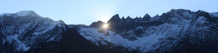 Besneeuwde bergtoppen met zonnestralen die door het gat in de berg vallen