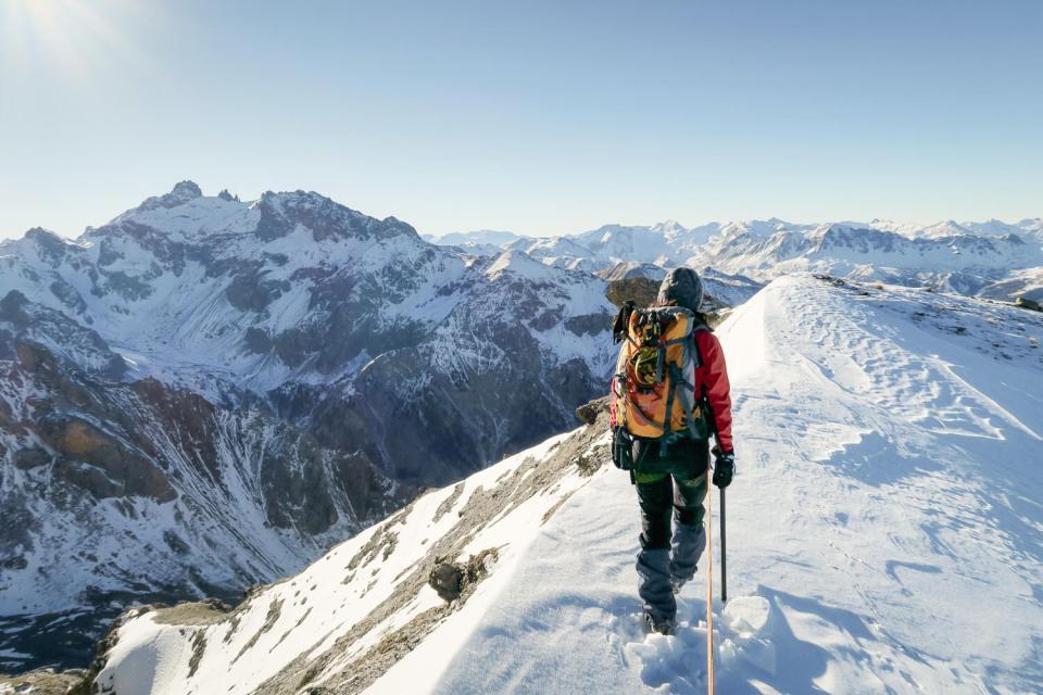 Femme marchant de dos sur la crête de la Main de Dieu dans une course d'alpinisme, dans le Queyras