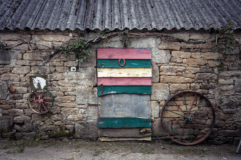 Petite porte ancienne en bois peinte de bandes multicolores, vue lors de mon road-trip en Bretagne dans le hameau de Kérampeulven