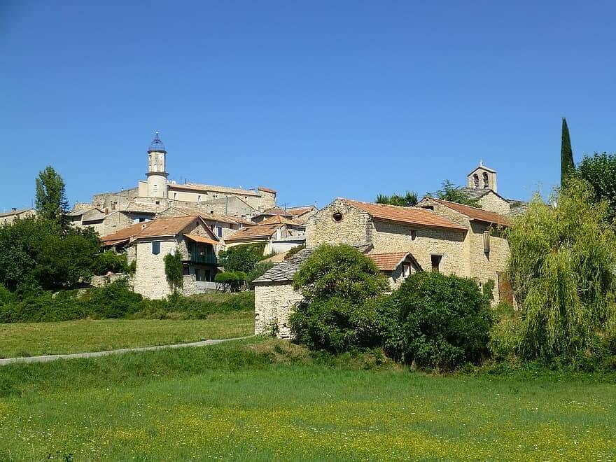 Petit village de provence verte avec maisons en pierre et champs d'herbe au premier plan