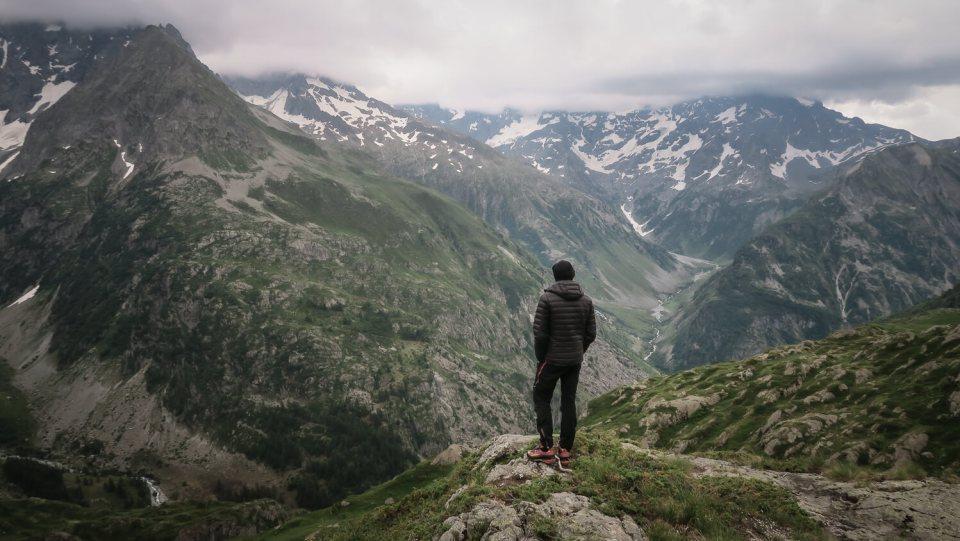 Homme de dos avec doudoune noire, bonnet et chaussures d'alpinisme devant un panorama de montagne (illustration du questionnement sur le renoncement)