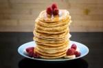 Pile de pancakes vegan avec framboises et bananes, sirop d'érable