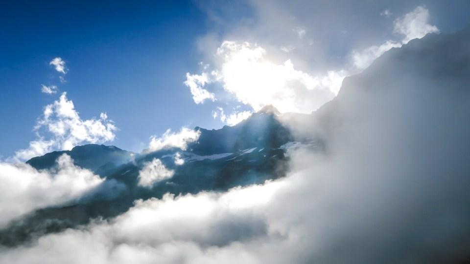 Sommet émergeant des nuages sur fond de soleil