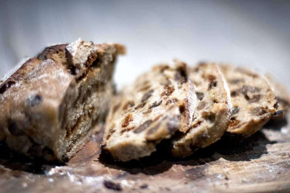 Pain de boulangerie bio aux baies de goji tranché, déposé sur une planche