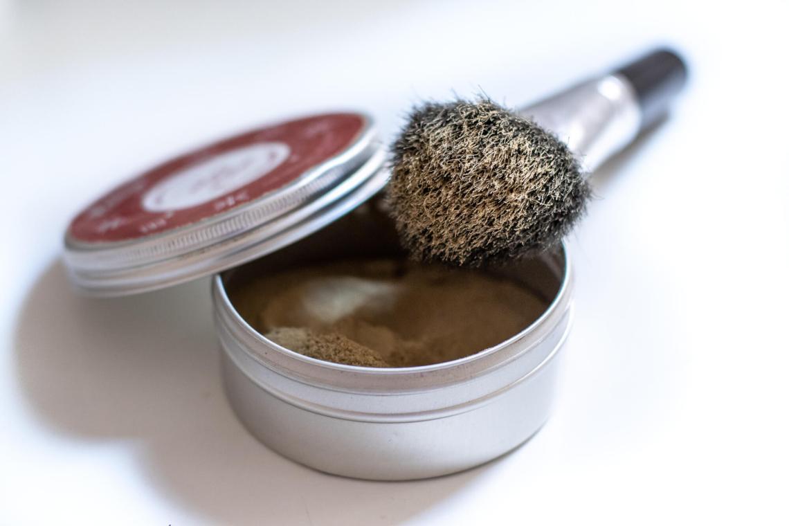 Shampoing sec maison dans un boite en fer blanc avec pinceau à maquillage.