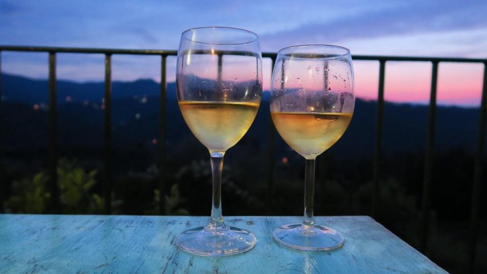 Deux verres de vin blanc frais photographiés sur fond de coucher de soleil rose