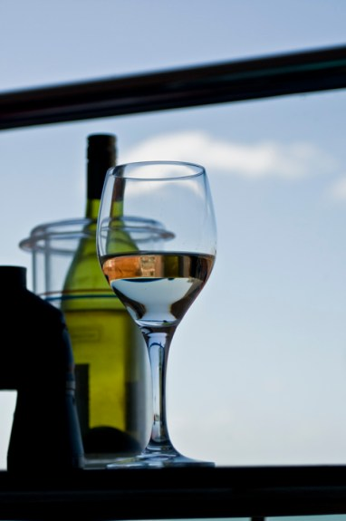Photo of wine glass and bottle against a blue sky