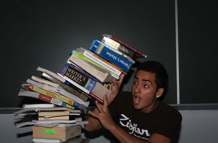 Joshua Rodrigez, Communications junior, gets crushed by textbooks. Many students  use alternative methods to buying textbooks such as renting, sharing, or avoiding them altogether. Photo by Zach Evans