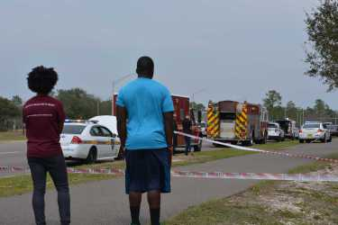Friends of Louissaint's watch as police investigate the scene. Photo by Julianne Brugger