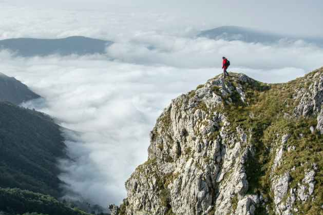 photography of person on green mountain high above cloud cover
