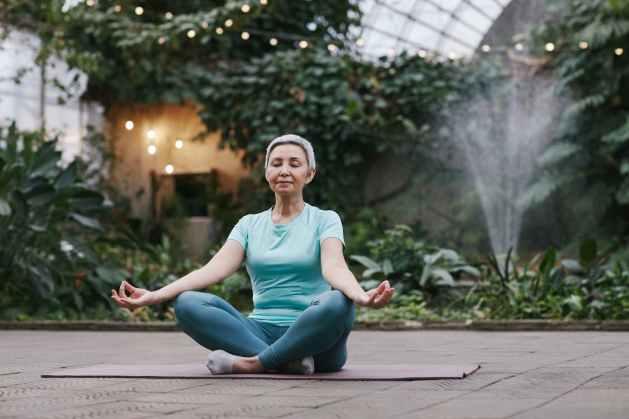 healthy woman meditating in garden