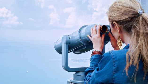 woman in blue denim jacket holding a gray steel tower viewer watching her thoughts to remove anxiety from her life
