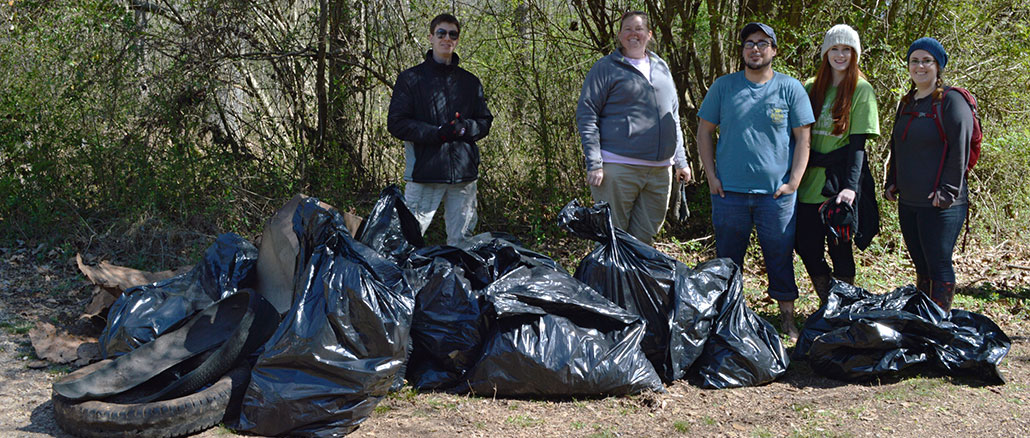 Students for Environmental Awareness show off their haul after a creek cleanup.