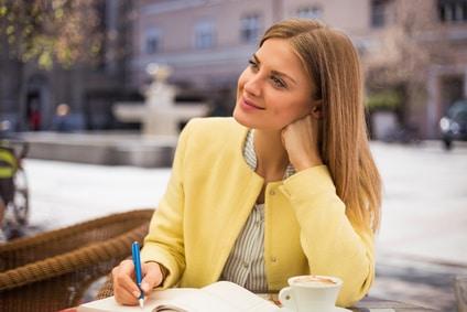 Eine junge Frau sitzt in einem Restaurant und lächelt zufrieden, denn sie hat ist hat es geschafft mit dem Hypnoseprogramm der unibee Institute schlank und gesund zu sein. Sie hat lange hellbraune Haare und trägt eine gelbe Jacke mit weißer Bluse darunter.
