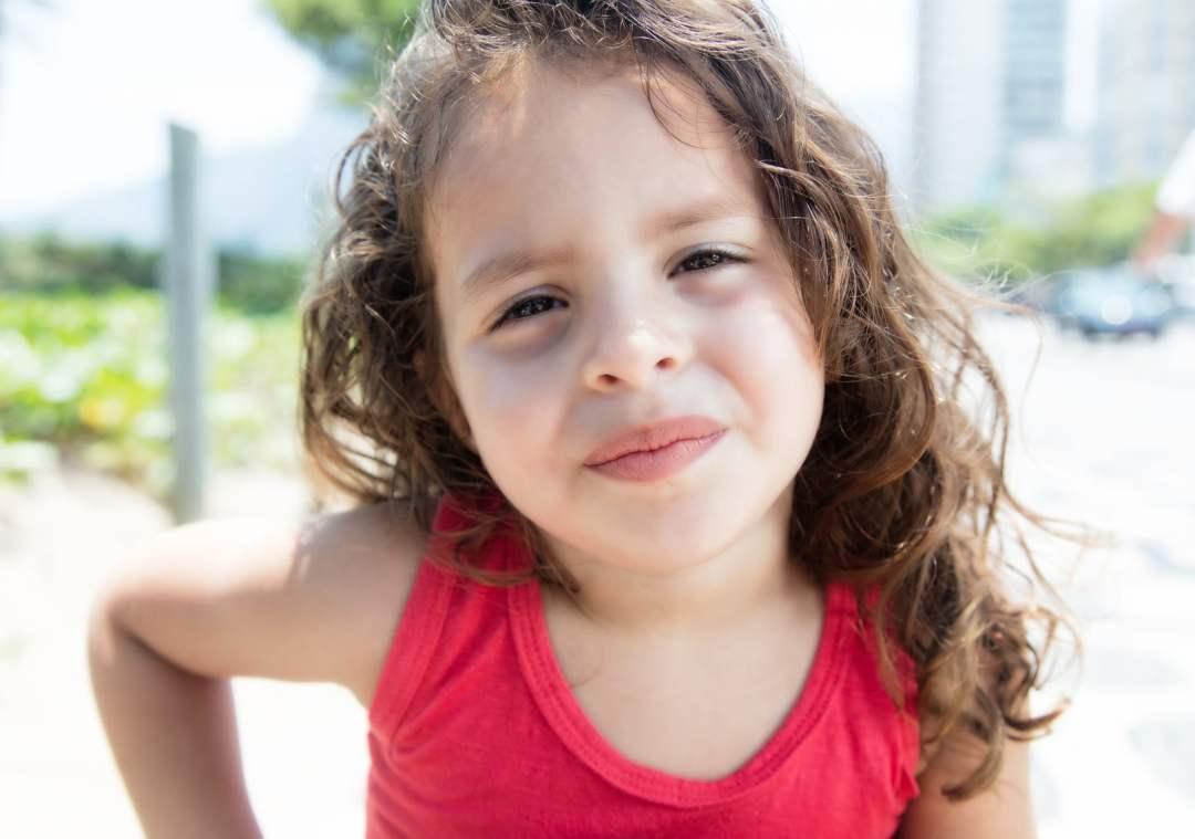 Auf diesem Bild ist ein kleines Mädchen im Alter von ungefähr 6 Jahren zu sehen. Es hat lange braune, gelockte Haare und ist mit einem roten Ärmellosen Shirt bekleidet und es ist ein Sommertag. Das Kind strahlt mit der Gesichtsmimik und Körperhatung ein gutes Selbstbewusstsein aus.