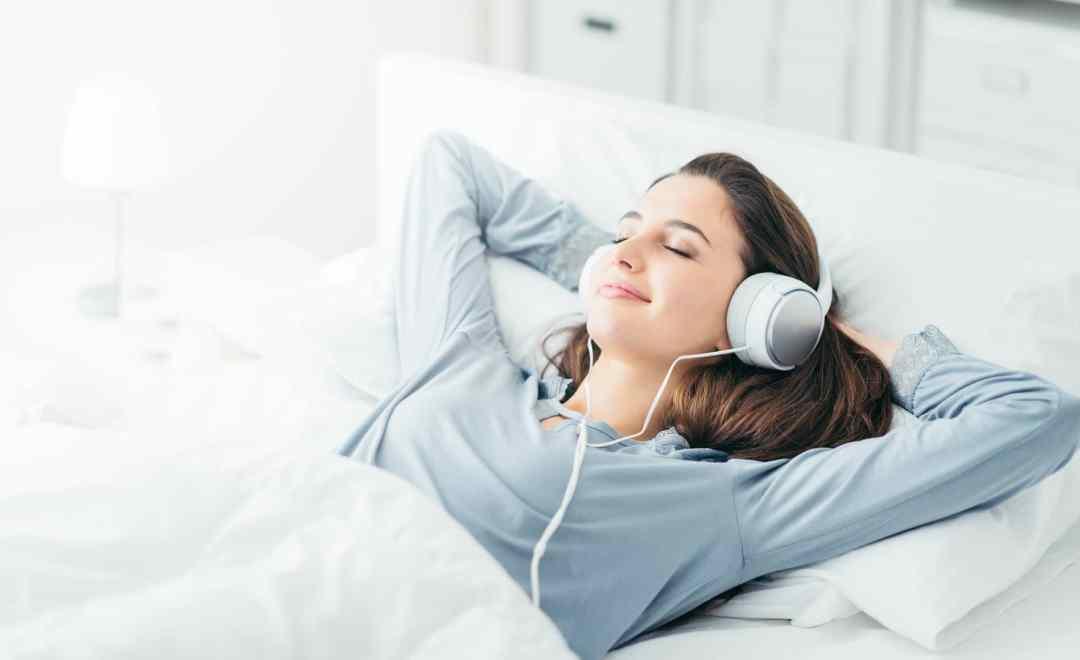Erklärbild: Junge Frau liegt im Bett und hört sich eine Hypnose zum Selbstbewusstsein stärken an.